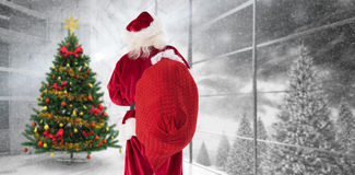 Composite image of santa is holding his bag in one hand royalty free stock photography
