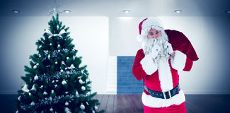 Composite image of santa holding sack and keeping a secret Royalty Free Stock Image