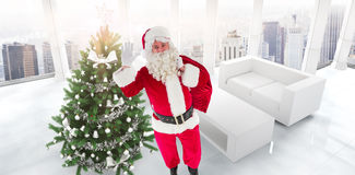 Composite image of santa holding a sack and waving Royalty Free Stock Photography