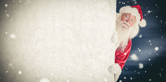 Composite image of santa looks out behind a wall Stock Photography