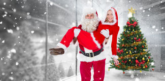 Composite image of santa and mrs claus smiling at camera. Santa and Mrs Claus smiling at camera against home with christmas tree stock photos