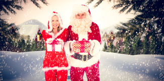 Composite image of santa and mrs claus smiling at camera offering gift Stock Photography