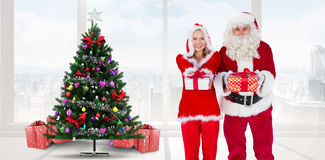 Composite image of santa and mrs claus smiling at camera offering gift. Santa and Mrs Claus smiling at camera offering gift against home with christmas tree stock images