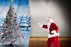 Composite image of santa pulls something with a rope Royalty Free Stock Image