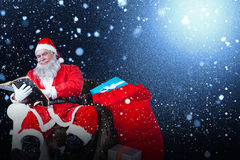 Composite image of santa reading bible with sack of christmas present beside him Stock Photos