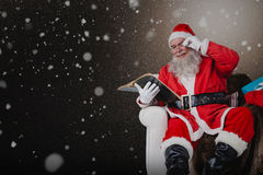 Composite image of santa reading bible with sack of christmas present beside him Stock Images