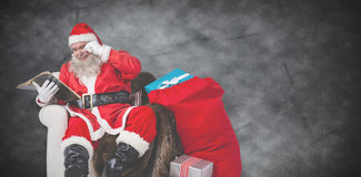 Composite image of santa reading bible with sack of christmas present beside him Stock Photography