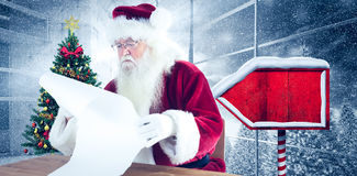 Composite image of santa reads a long list Stock Image
