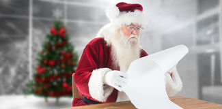 Composite image of santa reads a long list Royalty Free Stock Photos