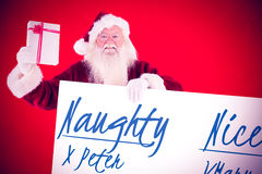 Composite image of santa shows a present while holding sign. Santa shows a present while holding sign against red background Stock Image
