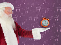 Composite image of santa shows something to camera. Santa shows something to camera against purple reindeer pattern Stock Photo