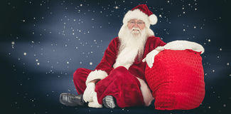 Composite image of santa sits next to his bag Royalty Free Stock Photos