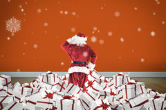 Composite image of santa standing on pile of gifts Stock Images