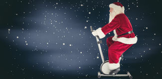 Composite image of santa uses a home trainer Royalty Free Stock Image
