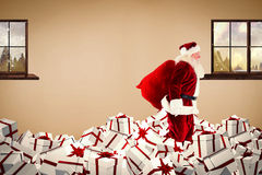 Composite image of santa walking on pile of gifts Royalty Free Stock Photography