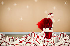 Composite image of santa walking on pile of gifts Stock Images