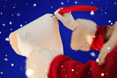 Composite image of santas hand writing list with a quill Stock Image