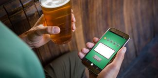 Composite image of satisfaction. Satisfaction against cropped hands of man using phone while having beer Stock Photo