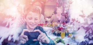 Composite image of scenic view of snow covered trees. Scenic view of snow covered trees against young boy holding smartphone during christmas dinner Stock Photo