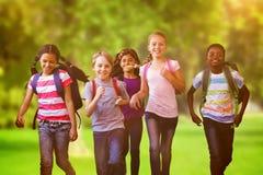Composite image of school kids running in school corridor Royalty Free Stock Photos