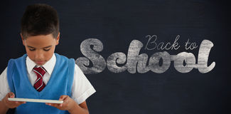 Composite image of schoolboy using digital tablet Royalty Free Stock Image