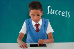 Composite image of schoolboy using digital tablet at table Stock Photos