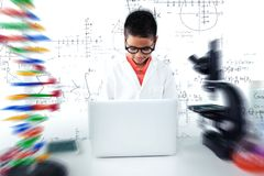 Composite image of schoolboy using laptop at desk stock photography