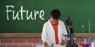 Composite image of schoolboy writing on note pad. Schoolboy writing on note pad against greenboard on wall Stock Photo