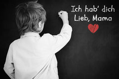 Composite image of schoolchild with blackboard. Schoolchild with blackboard against german mothers day message Stock Photo