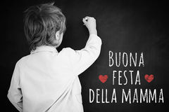 Composite image of schoolchild with blackboard. Schoolchild with blackboard against italian mothers day message Stock Images