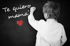 Composite image of schoolchild with blackboard. Schoolchild with blackboard against spanish mothers day message Royalty Free Stock Image