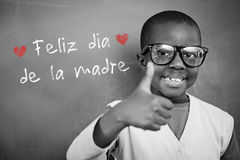 Composite image of schoolchild with blackboard. Schoolchild with blackboard against spanish mothers day message Stock Photos