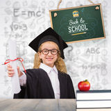 Composite image of schoolgirl with graduation robe and holding her diploma Stock Photo