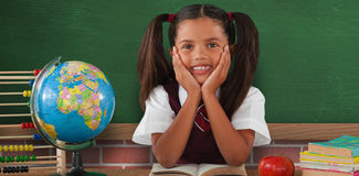 Composite image of schoolgirl leaning by globe and books Royalty Free Stock Photos