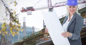 Composite image of selfassured businesswoman wearing a helmet Stock Image
