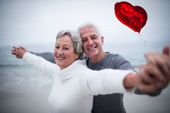 Composite image of senior couple on beach and red heart balloon 3d Stock Photos