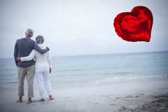 Composite image of senior couple on beach and red heart balloon 3d Royalty Free Stock Image