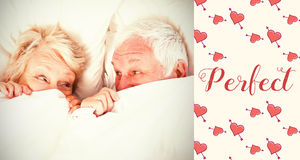 Composite image of senior couple in bed and valentines words. Valentines words against overhead view of couple hiding in blanket Stock Image