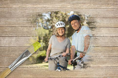 Composite image of senior couple on bikes in the park Stock Photography
