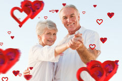 Composite image of senior couple dancing on the beach. Senior couple dancing on the beach against love heart pattern royalty free stock images