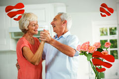Composite image of senior couple dancing and hearts 3d Stock Photos