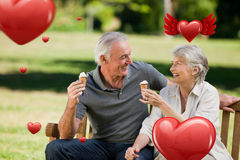 Composite image of senior couple eating an ice cream on a bench. Senior couple eating an ice cream on a bench against hearts Royalty Free Stock Images