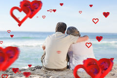 Composite image of senior couple looking at the sea. Senior couple looking at the sea against love heart pattern royalty free stock photo