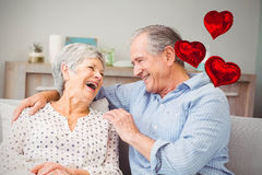 Composite image of senior couple and love heart balloons 3d. Love heart balloons against romantic senior couple laughing while sitting on sofa 3d Royalty Free Stock Image