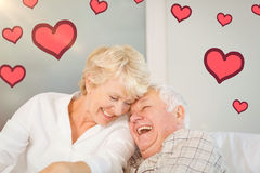 Composite image of senior couple and valentines hearts 3d. Red Hearts against cheerful senior couple laughing Royalty Free Stock Image