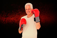 Composite image of senior man in boxing gloves. Senior man in boxing gloves against dark background Royalty Free Stock Image