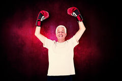 Composite image of senior man in boxing gloves. Senior man in boxing gloves against dark background Stock Images