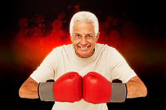 Composite image of senior man in boxing gloves. Senior man in boxing gloves against dark background Royalty Free Stock Images