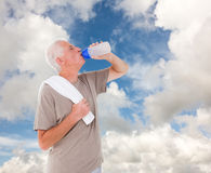 Composite image of senior man drinking from water bottle. Senior man drinking from water bottle against blue sky with white clouds Royalty Free Stock Images