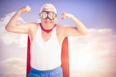 Composite image of senior man pretending to be a superhero. Senior man pretending to be a superhero against colored sky with clouds Royalty Free Stock Photo